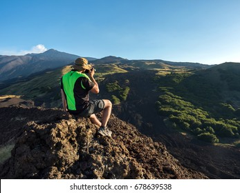 tourist photographer takes a panoramic picture of the beautiful valley of Etna Vulcano with, craters, vegetation and lava stone during an excursion . satured color filter