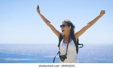 A tourist photographer woman holds a phone, feels free with a backpack on her back, a wonderfully beautiful view of the blue sea and sky. Concept: travel, vacations, freedom, telephone communication.