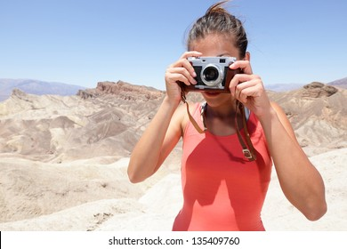 Tourist photographer woman taking pictures photo in Death Valley desert landscape of Zabriskie Point in Death Valley National Park, California, USA. Young woman on travel in United States.