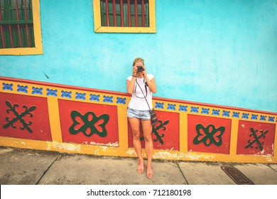 Tourist photographing the colourful streets in Guatape, Colombia