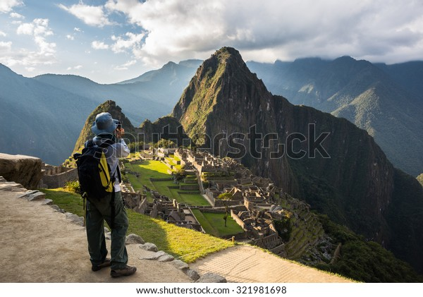 Tourist photographing Machu Picchu illuminated by the last sunlight from above with smartphone. Scenic sky with clouds and sun rays. Concept of sharing travel moments using technology.