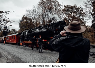 Tourist photographing old historic steam locomotive
