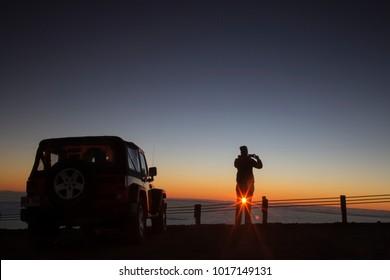 Tourist photographing sunrise at summit of Mauna Kea - Hawaii