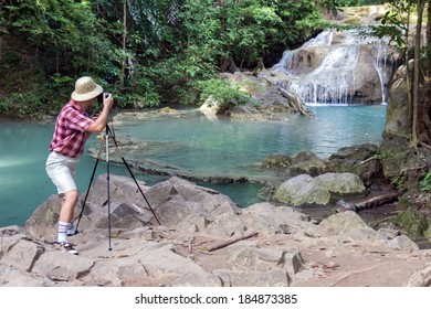 tourist photographing waterfall