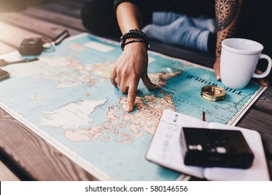 Tourist planning vacation with the help of world map with other travel accessories around. Young woman pointing at North America on the world map. - Shutterstock ID 580146556