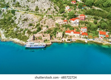Tourist pleasure yacht near the houses on the rocky shore, top view