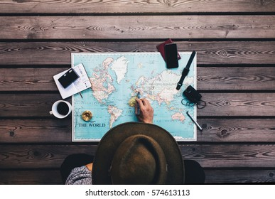 Tourist pointing at Europe on world map surrounded with binoculars, compass and other travel accessories. Man wearing brown hat planning his tour looking at the world map.