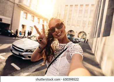 Tourist posing for a selfie in a street flashing victory sign. Vlogger recording content for her travel vlog.