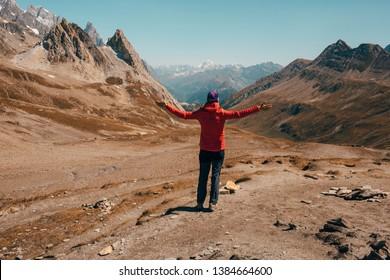 tourist with raised hands standing at mountain pass Col de la Seigne.