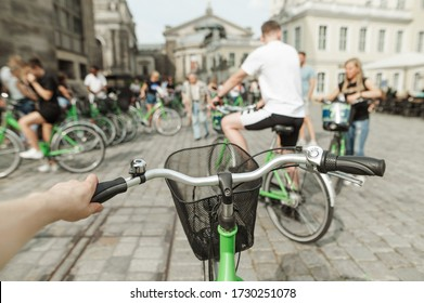 Tourist with a rented bicycle stands on the street of a European place, the view from the first face, holding the handlebars. Cycling around the European town concept.