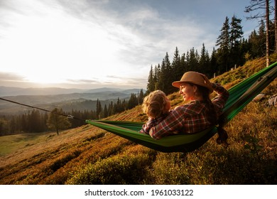 tourist resting in a hammock in the mountains at sunset - Shutterstock ID 1961033122