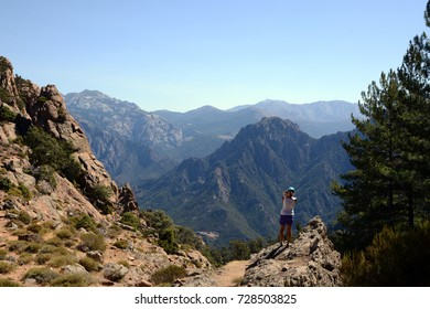 Tourist resting and watching the mountains, Corsica