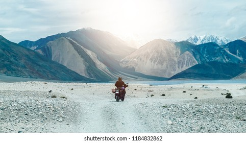 Tourist riding an adventure big bike motorcycle on tuff and bumpy road on rock mountain in clear beautiful lightning to explore the world, with copy space