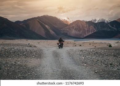 Tourist riding an adventure motorcycle on tuff and bumpy road on rock mountain in sunset lightning to explore the world, with copy space
