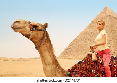Tourist riding camel in Giza. Young blonde woman near Pyramid of Khafre, Egypt