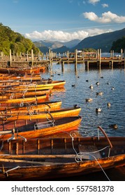 Tourist rowing boats lined up on the shore of Derwent Water at Keswick Launch in England's Lake District National Park.