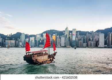 Tourist sailboat crosses Victoria harbor from Kowloon side to the Hong Kong Island. Scenic view of traditional Chinese wooden sailing ship with red sails. Skyscrapers of downtown in background.