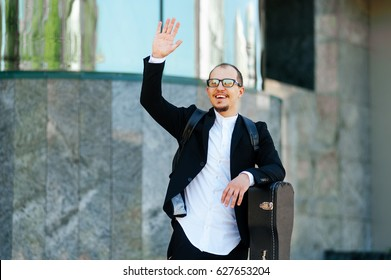 Tourist saluting on unfocused background. Man waving hand say hello to his friend in modern city street. Businessman say hello. Man with glasses. Hello gesture.