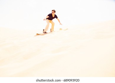 Tourist Sandboarding In The Desert