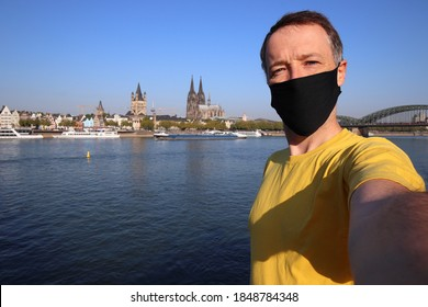 Tourist selfie with face mask in Cologne city, Germany. Traveler selfie with Cologne skyline.