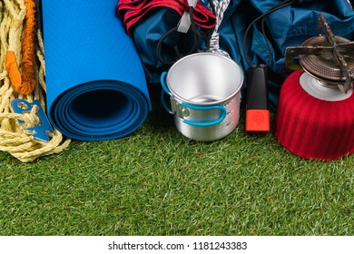 tourist set on a green lawn for a hike in an expedition, with utensils for cooking in the open air