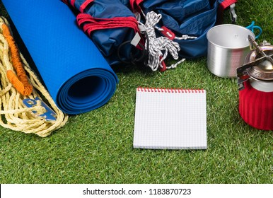 tourist set on a green lawn for a hike in an expedition, with utensils for cooking food outdoors, with a place for writing, on a white sheet