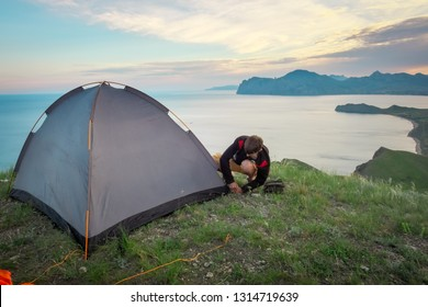 Tourist sets up a tent on the top of a mountain overlooking the sea