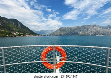 Tourist ship approaching bay on clear summer day - view from upper deck with the bulwark and life buoy. Traveling and tourism concept background.
