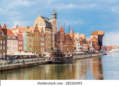 Tourist ship and colourful historic houses reflection Motlawa river in port of Gdansk, Baltic Sea, Poland.
