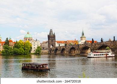 Tourist the ship floats under Charles bridge, Prague, Czech Republic