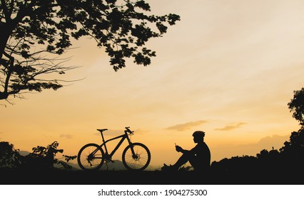 A tourist silhouette with a bicycle sitting Resting on the mountain in the evening