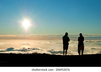 Tourist silhouette watching sunset on the top of  Haleakala volcano on Maui Hawaii