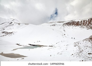Tourist silhouettes are walking down the snow path at beautiful cloudy sky background. Outdoor climbing concept.