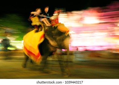 Tourist sit on elephan go around Phuket Fantasea Theater Hall at night. Take a photo by slow shutter and panning.