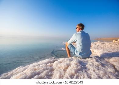 Tourist sits on the shore of the Dead Sea. Jordan landscape