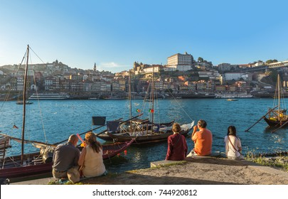 Tourist sitting beside douro river with porto wine port old town background,Portugal