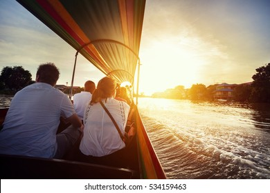 Tourist sitting in long-tail boat cruise by Chao Phraya river in Ancient city Ayutthaya at Sunset, Thailand