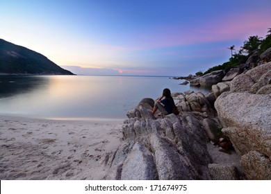 Tourist sitting on the beach and watching a breathtaking sunset at Haad Khuad, Koh Phangan, Southern Thailand. Blurred motion on water surface due to long exposure.