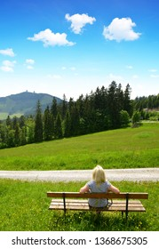 Tourist sitting on a bench overlooking the mount Grosser Arber in National park Bayerische Wald, Germany.