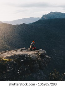 Tourist sitting on the rock with a beautiful sunrise at the Balconies in the Grampians National Park, Victoria, Australia.