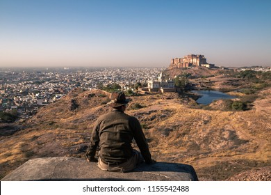 tourist sitting on rock on top of the hill with beautiful view of Jaswant Thada , Mehrangarh fort and city of Jodhpur in background, this photo was taken on viewpoint of Jodhpur in Rajasthan India