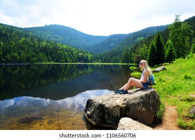 Tourist sitting on stone by moraine lake Kleiner Arbersee in National park Bavarian forest. Germany.