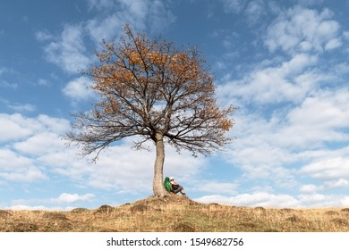 Tourist sitting under majestic orange tree at autumn mountain valley. Dramatic colorful fall scene with blue cloudy sky. Landscape photography
