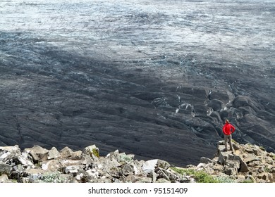 Tourist at Skaftafell is admiring a mighty glacier blackened from volcanic ash in Vatnajökull National Park, Iceland