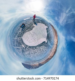 tourist with sleds walks along the blue ice of Lake Baikal. Spherical 360 panorama little planet.