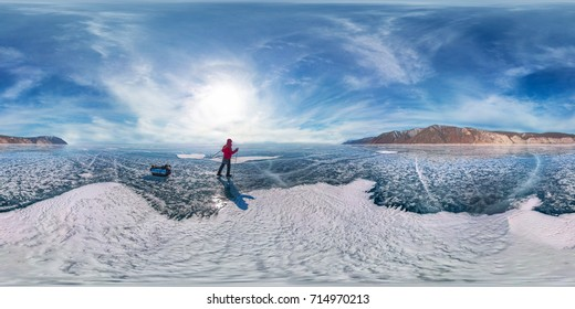 tourist with sleds walks along the blue ice of Lake Baikal. Spherical 360 degrees 180 panorama.