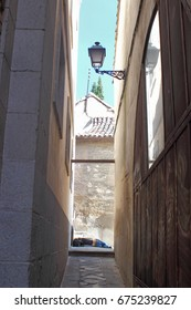 Tourist sleeping drunk in a typical narrow street of the city of Toledo, Spain, a world heritage site,