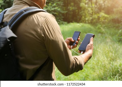 Tourist with smartphone and battery charger is looking for the way in summer forest. Guy with powerbank is lost in the nature. Modern technologies concept to stay always online and in touch.