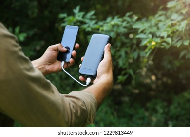 Tourist with smartphone and battery charger is walking in the summer forest. Guy with powerbank is lost in the nature. Modern technologies concept to stay always online and in touch.