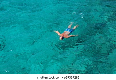 A tourist snorkeling in Seychelles wild beach birds eye view
